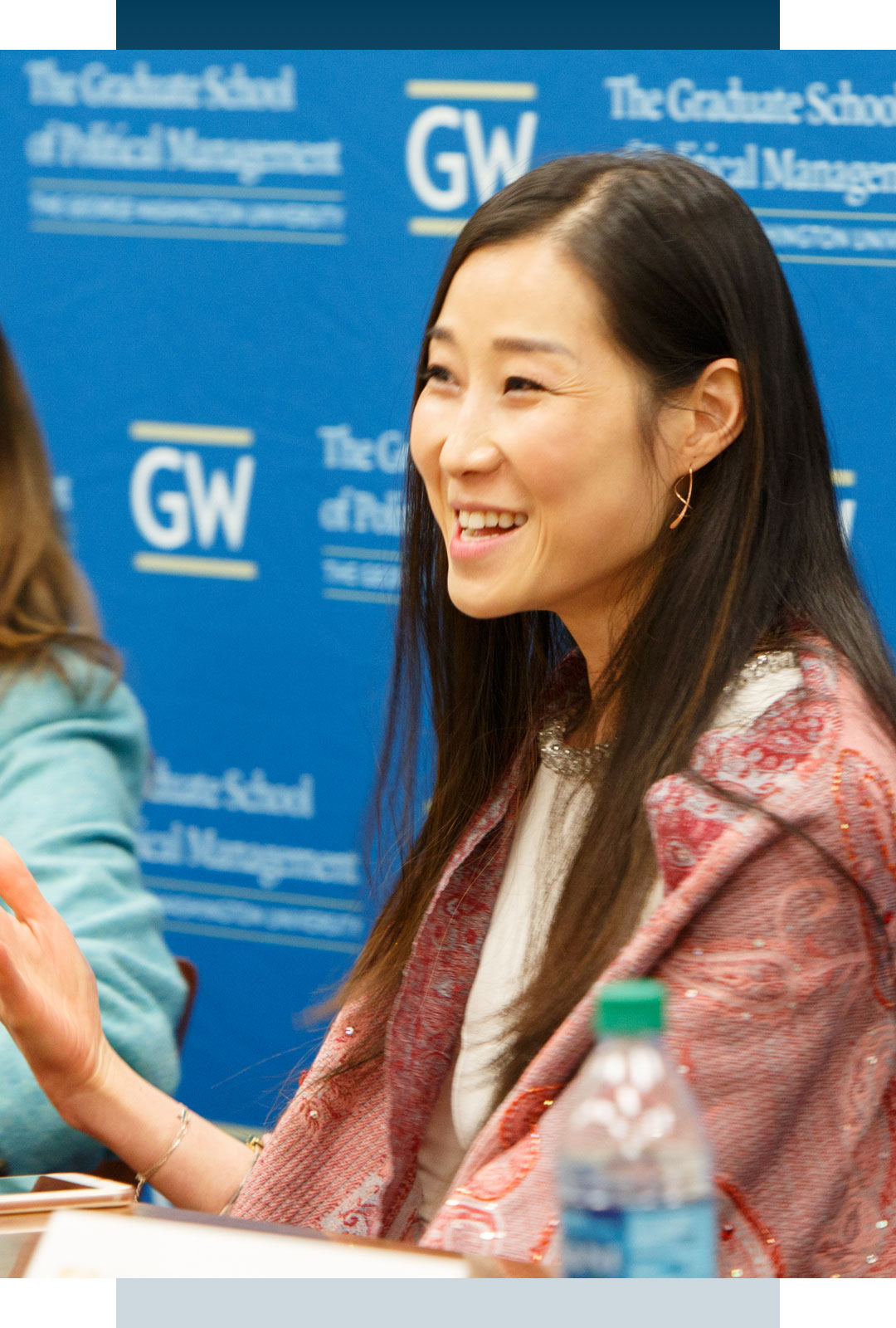 Woman speaking at a table; backdrop has GW logo and words The Graduate School of Political Management