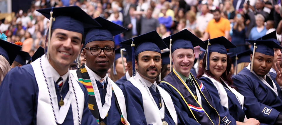 graduation in Smith Center with a group of male and female graduates smiling in graduation hats and gowns