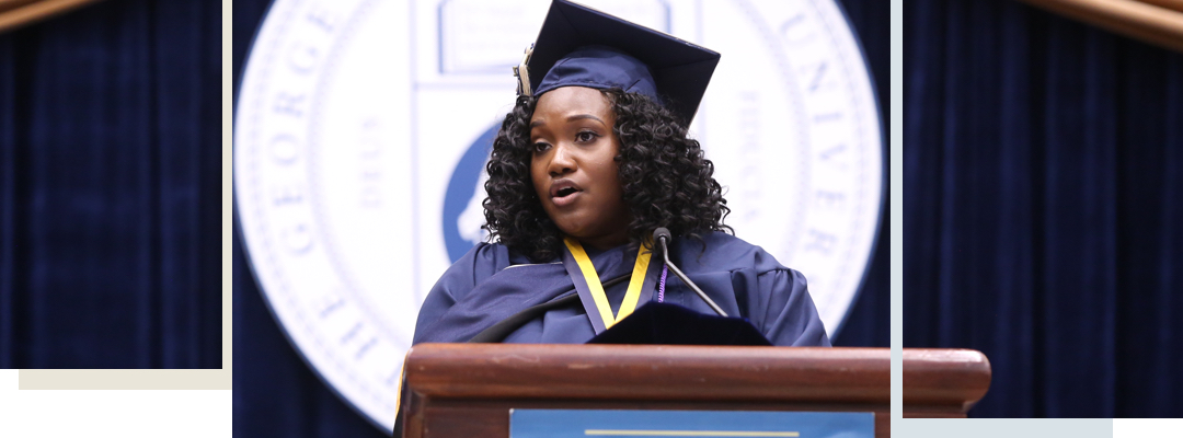 Student speaking at commencement, Seal with The George Washington University project behind her