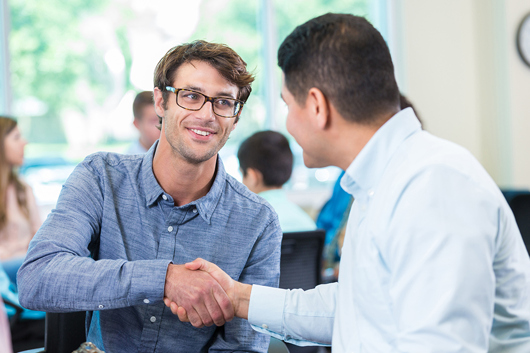 Career coach meeting with student, two men shaking hands