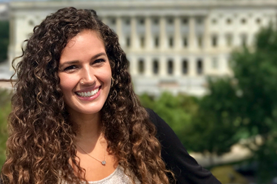 Elizabeth Rule with long brown curly hair in front of the U.S. Capitol