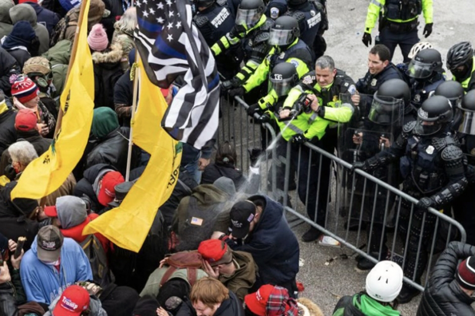 violent mob of people with barrier and police