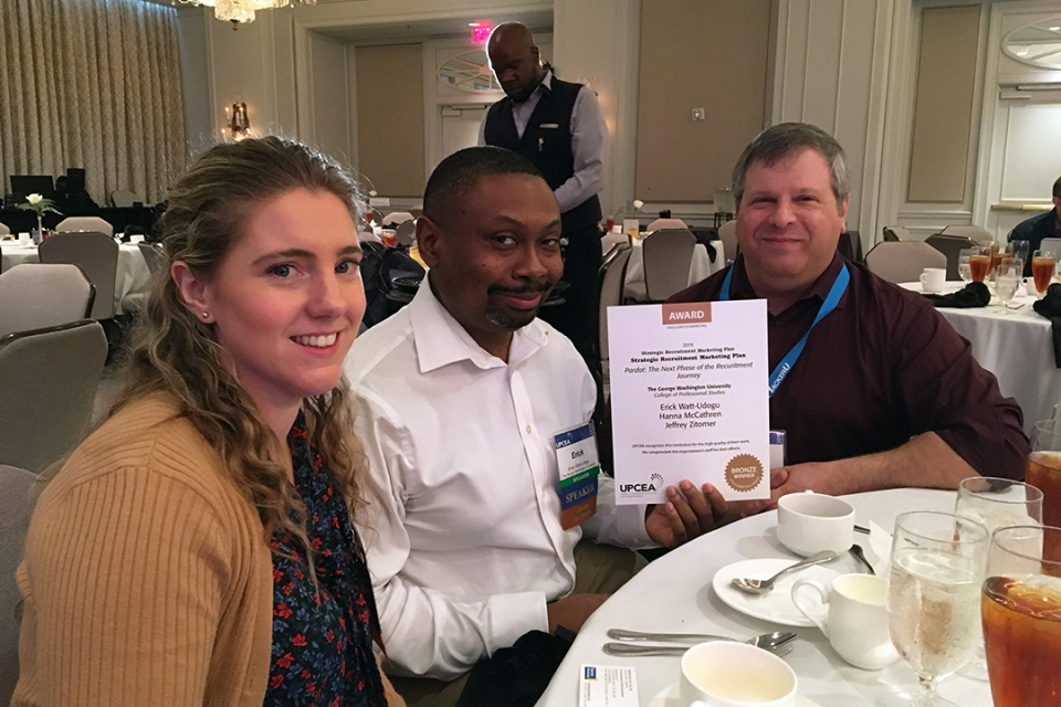 CPS marketing team holding award certificate at lunch in ballroom