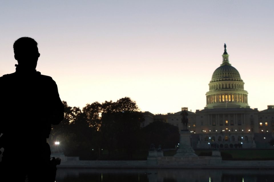 security person's back with White House sillhoute at dusk