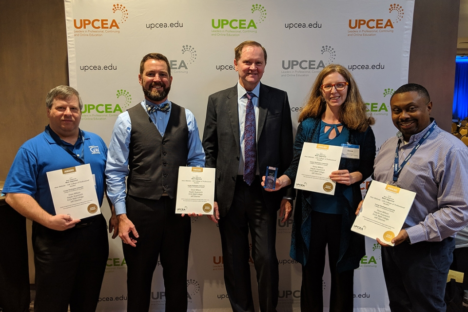 4 CPS Marketing team members and UPCEA president pose with award certificates.