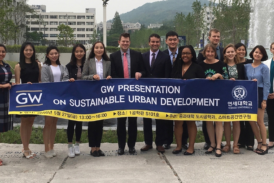 SUP student group with Program Director John Carruthers hold banner with words Sustainable Urban Planning Program, GW