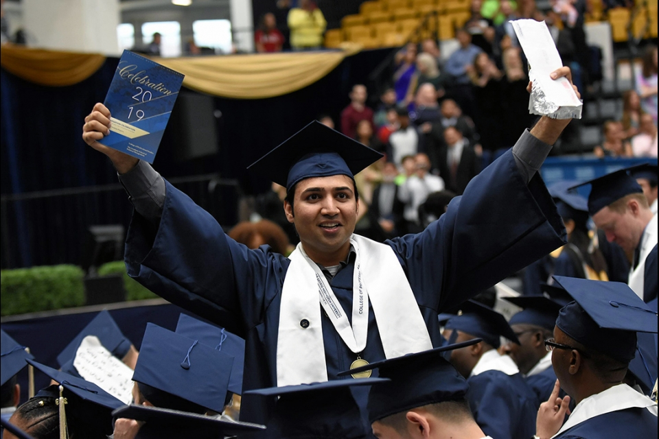 Happy male graduate with arms up in the air