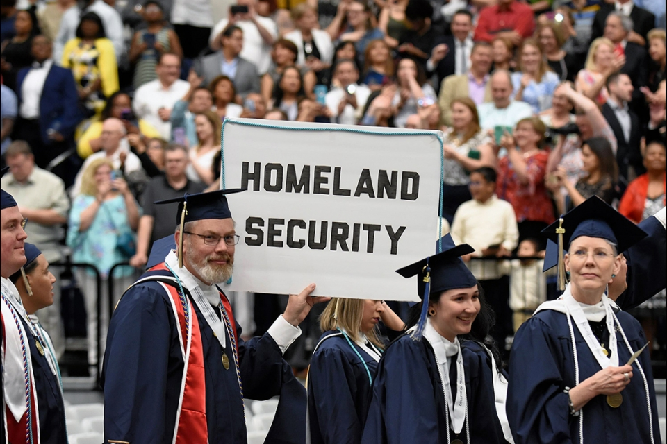 Homeland Security students with sign during processional