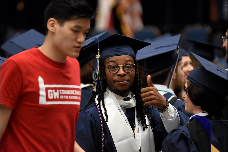 Female African American graduate in cap and grown with thumbs up