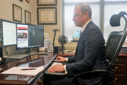 Dr. Todd Belt in a dark suit, white shirt and glasses in his office looking at a computer monitor watching Michael Cohen testify