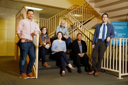 Photo with 6 people, mix of men and women, posing by staircase with metal railings