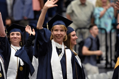 Female graduates waving