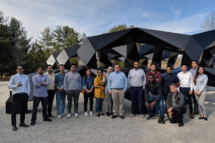 Large IIST student group of approximately 20 people in front of a black metal abstract sculpture