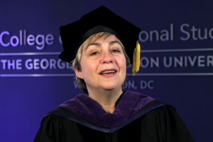 Toni Marsh wearing commencement gown and hat with tassel and part of College of Professional studies logo on a blue wall behind