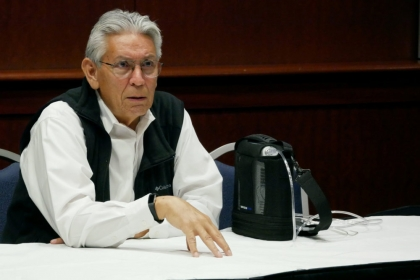 Kevin Gover speaks at GW, sitting at a table, white shirt, black vest, glasses