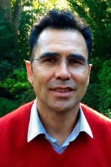Dark haired man with glases in red sweater and collared shirt