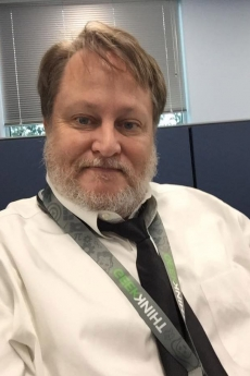 Todd Blanchard with grey beard and hair combed long with button down white shirt, tied and lanyard