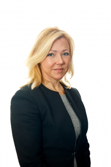 Woman with shoulder length blond hair in black tailored jacket and back and white top