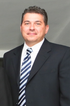 Jeff Delinksi in suit and blue and white diagonally striped tie with short hair