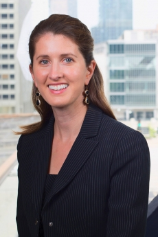Carrie Bill Riley headshot with glass windows and city buildings in the background