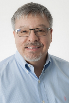 Headshot of man with salt and pepper hair and glasses in blue button down shirt