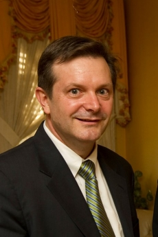 Dean Smith in dark suit, white shirt, shiny moss green tie and brown hair with curtains in the background