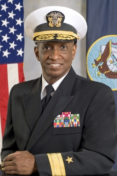 Norman Hayes in decorated U.S. Naval uniform and white cap with U.S. flag behind him