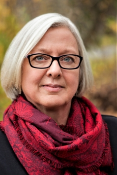headshot of woman with grey bob, glasses, red patterned scarf and multi colored background that looks like autumn leaves