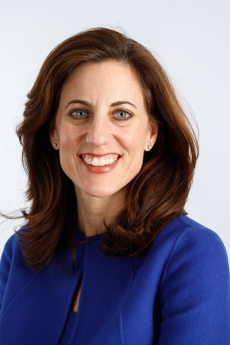 Woman smiling with long brown hair and blue eyes in medium blue tailored suit jacket