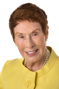 Headshot of woman with short red hair and yellow tailored suit jacket