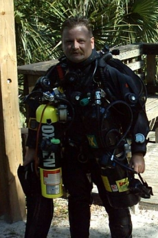 Roger Kuhn in black scuba diving outfit with oxygen tank and related equipment standing outside with plants behind him