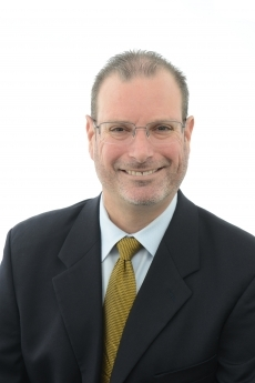 Todd Belt in dark suit, white button down shirt and mustard tie with short brown hair and glasses